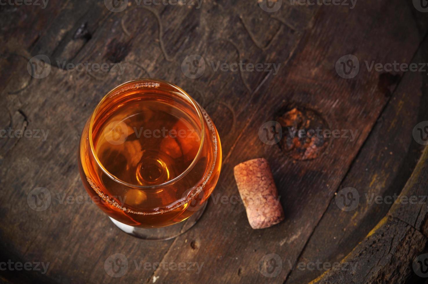 Glas Cognac auf dem Vintage Holzfass foto
