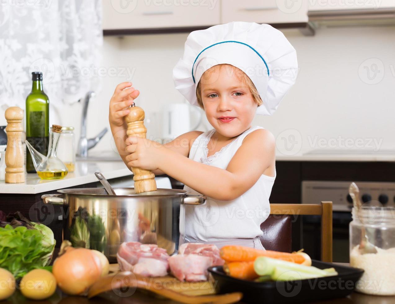 Kind kocht Suppe in der Pfanne foto