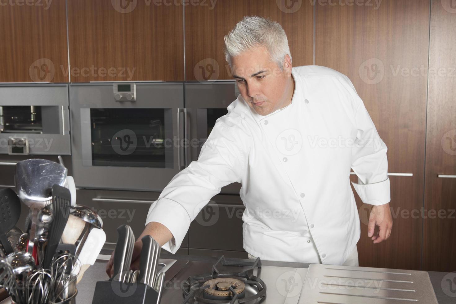 Koch, der für Messer in der gewerblichen Küche lehnt foto
