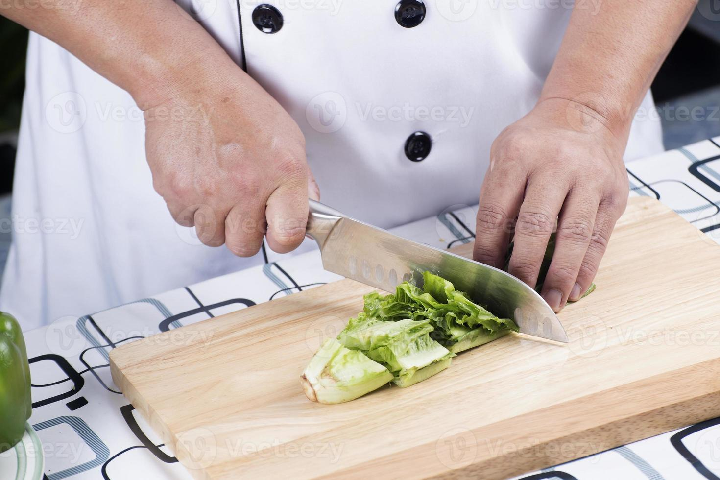 Koch, der Salat schneidet foto