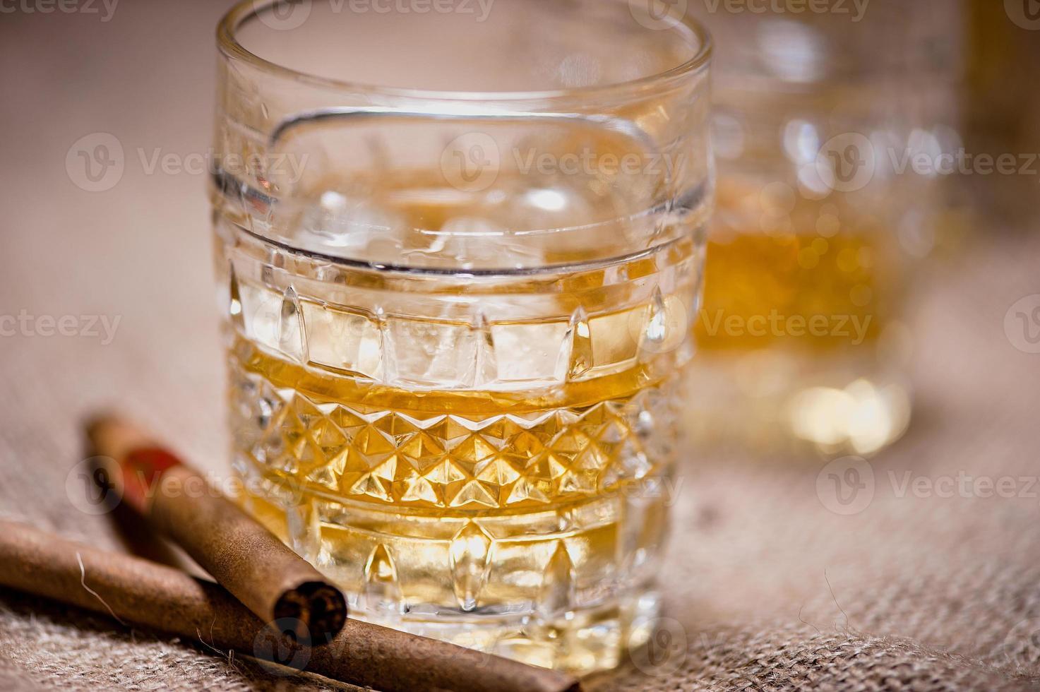 Nahaufnahme von Whiskyglas auf den Felsen mit Zigarren foto