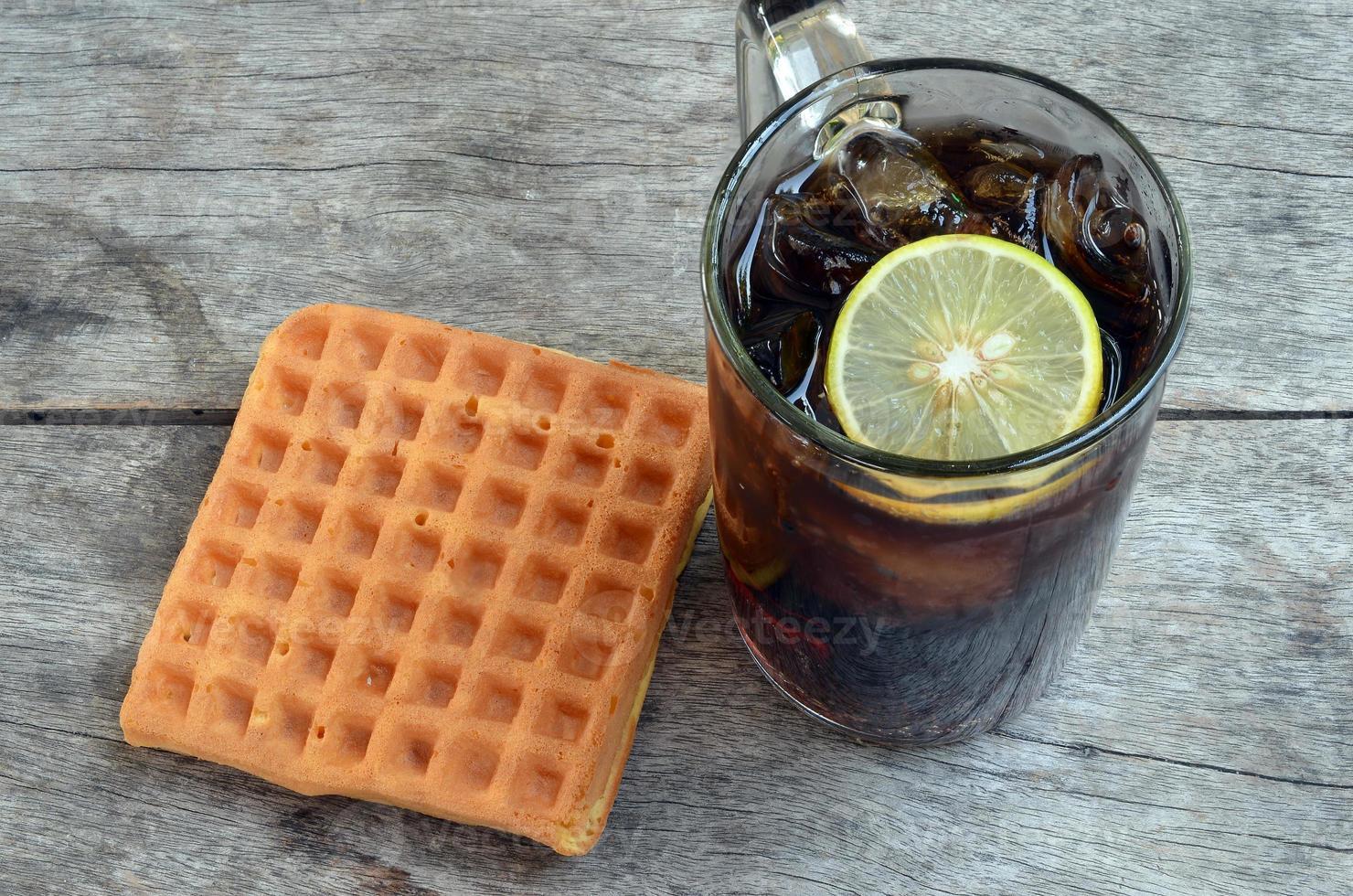 Cola mit Zitrone und süßen Waffeln foto