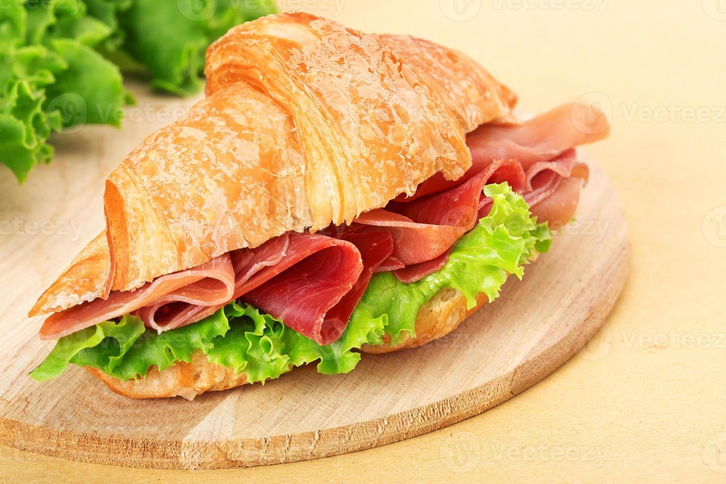 Croissant mit Parmaschinken und Salat auf Schneidebrett foto