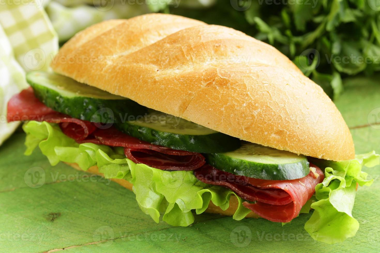 frisches Sandwich mit geräuchertem Fleisch, Gurke und Salat foto
