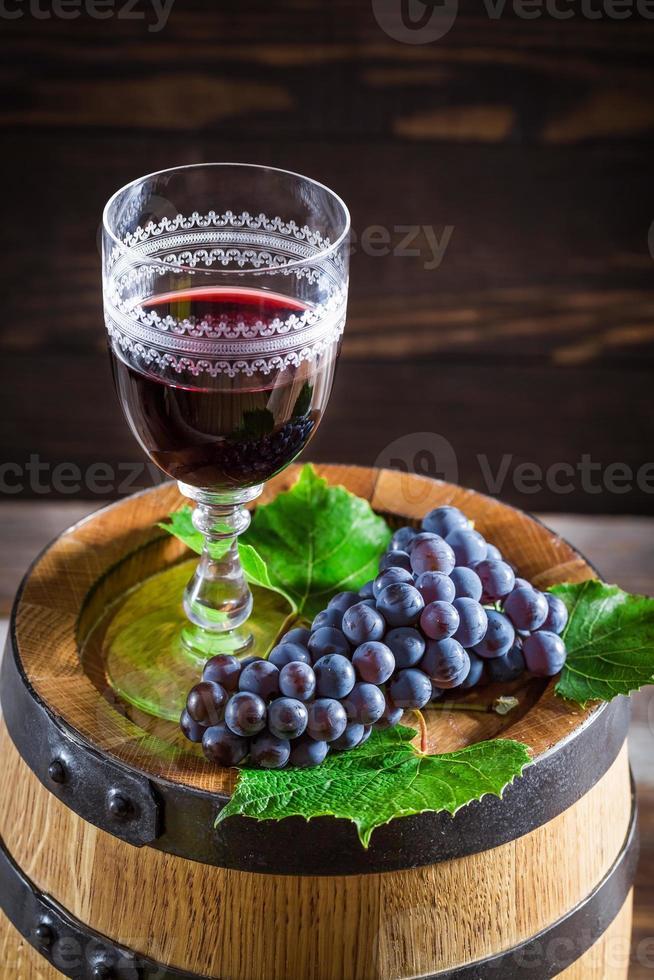 leckerer Wein im Glas mit Trauben foto