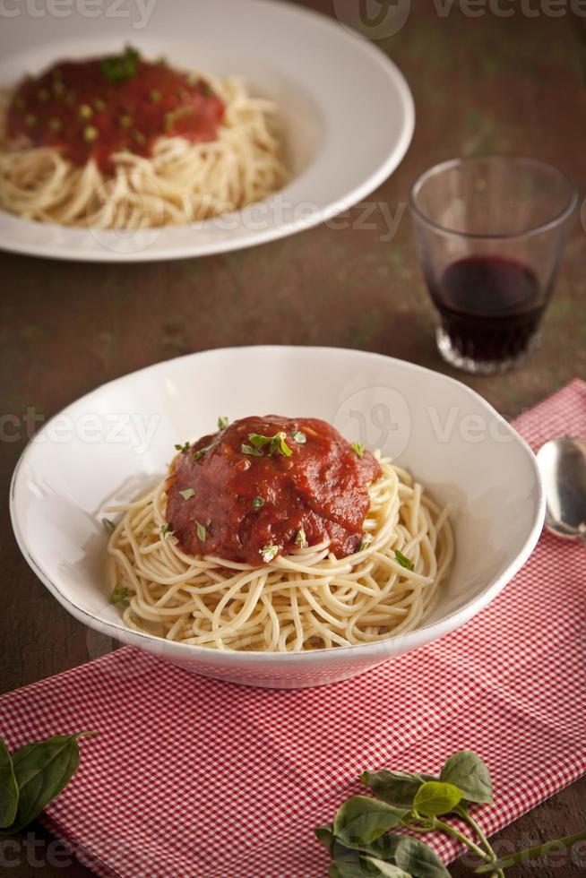 Spaghetti-Abendessen mit Tomatensauce und Basilikum aus der Nähe foto