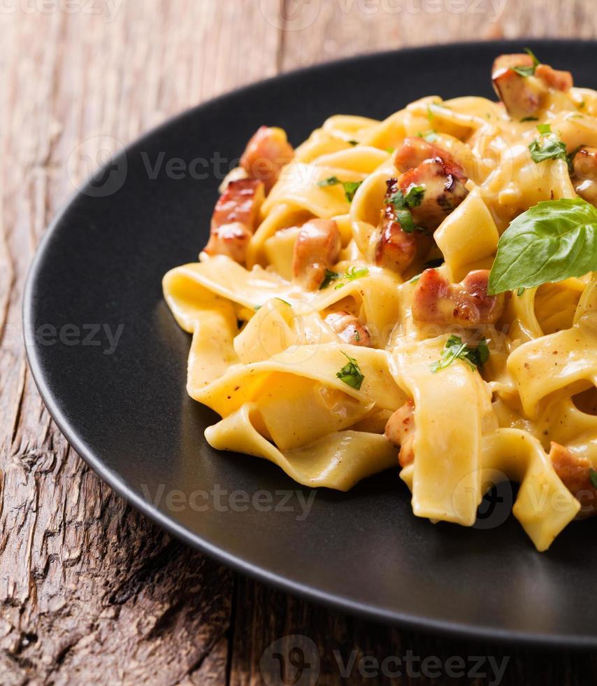 Pasta Carbonara mit Speck, Basilikum und Käse foto