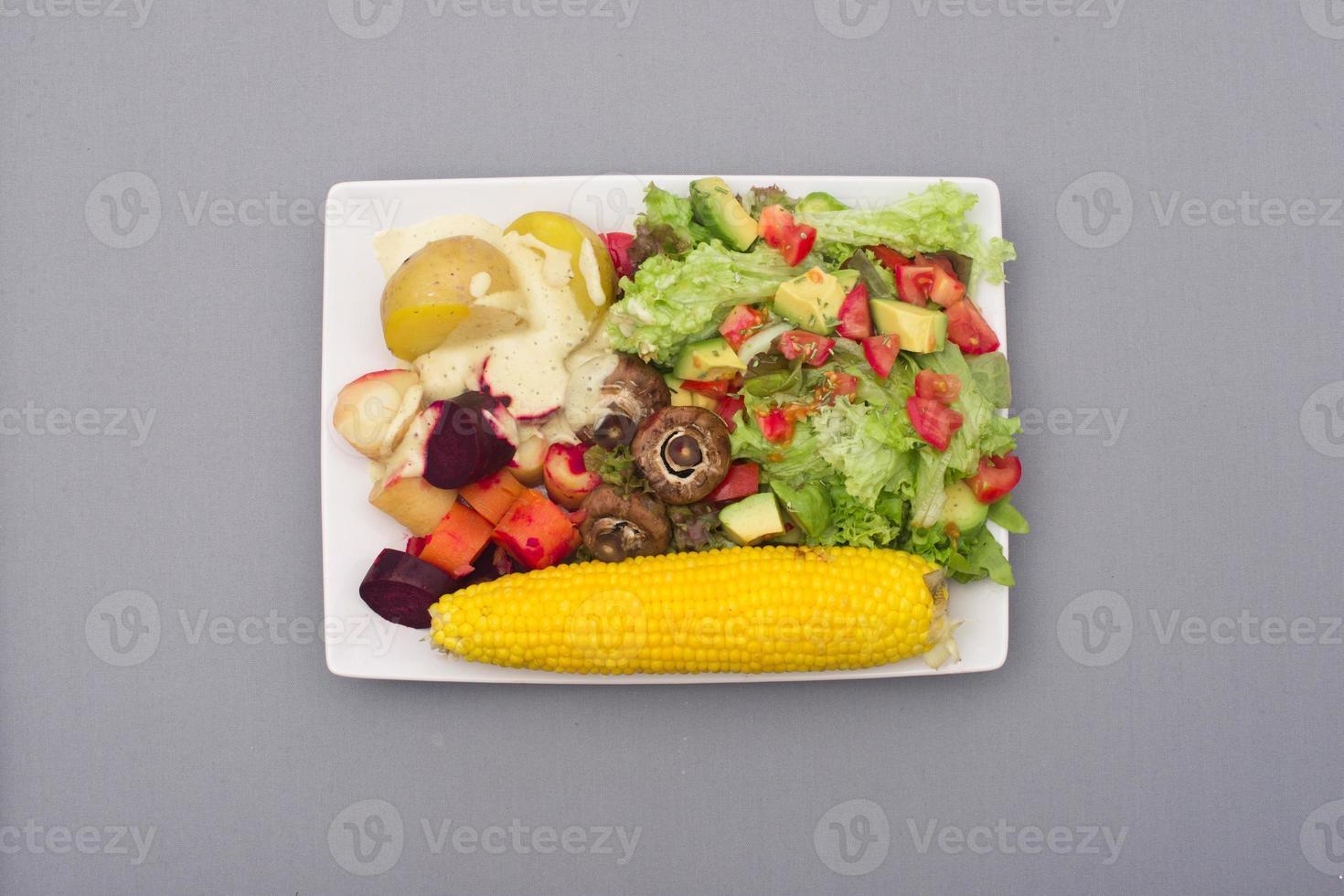 Salat mit Avocado und Tomate mit Kartoffeln, Wurzelgemüse und Mais foto