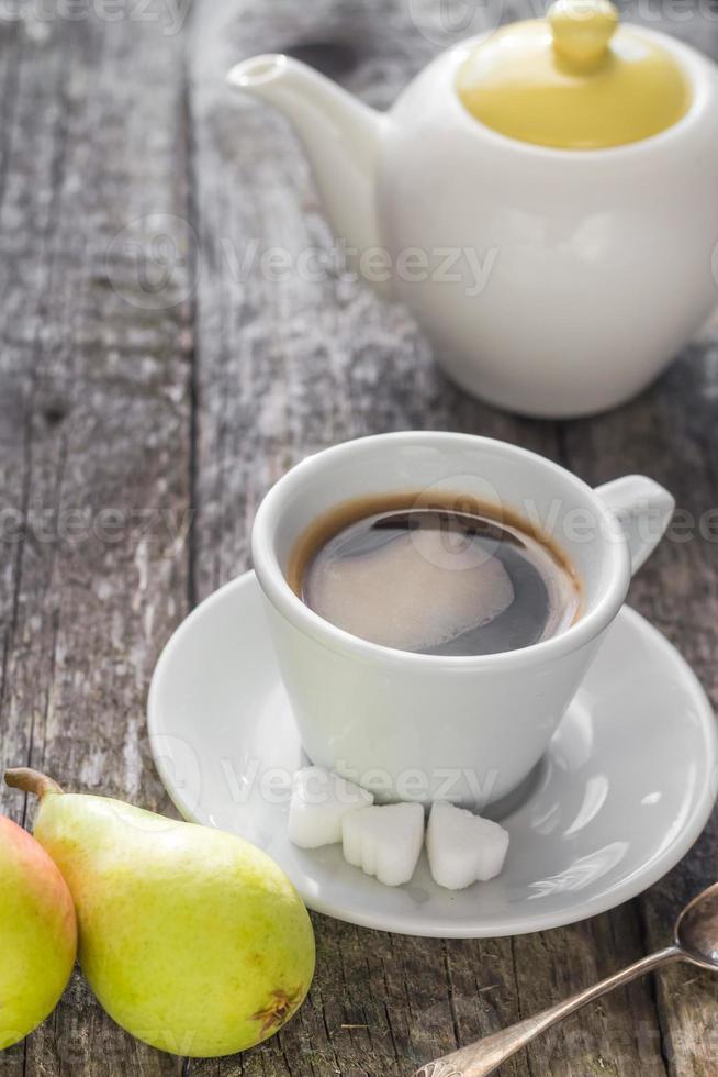Kaffeetasse schwarz Holzbrett braune Birnen weißer Krug foto