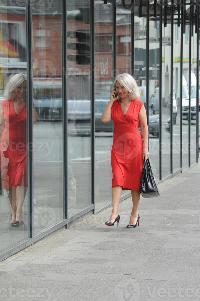 ältere Frau spricht am Handy foto