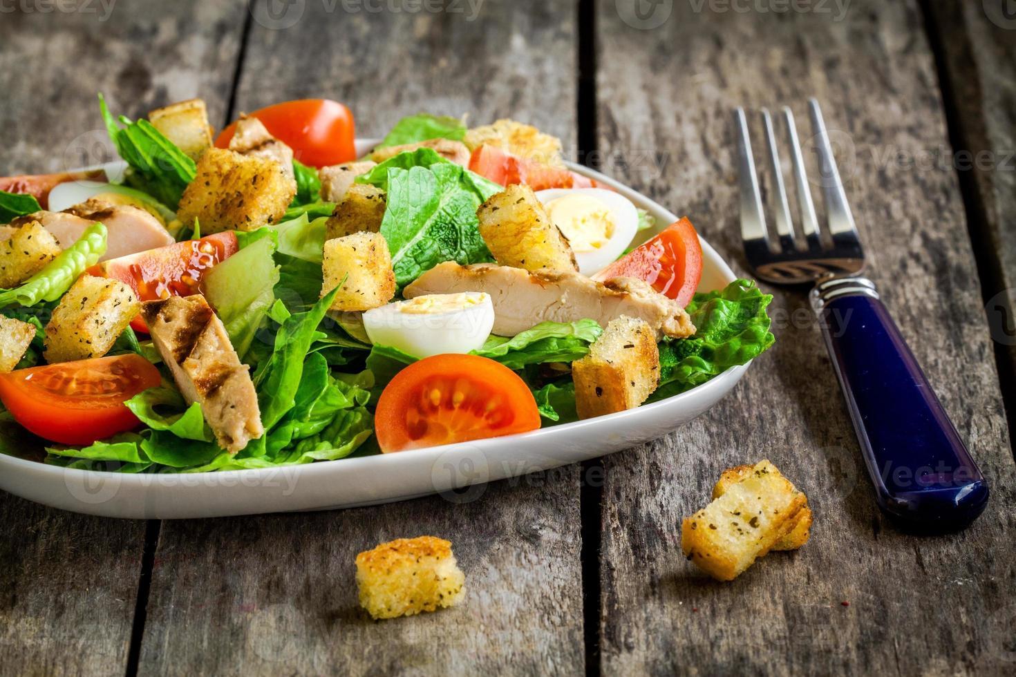 Caesar Salat mit Croutons, Wachteleiern, Tomaten und gegrilltem Hähnchen foto