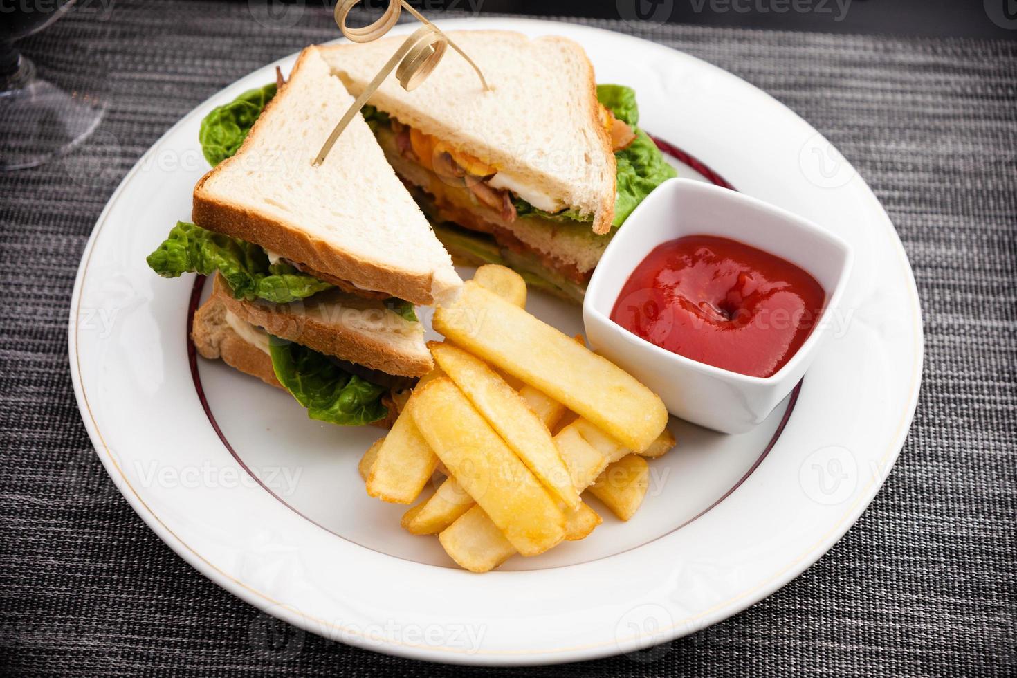 Sandwich mit Spiegeleiern, Speck und Salat foto