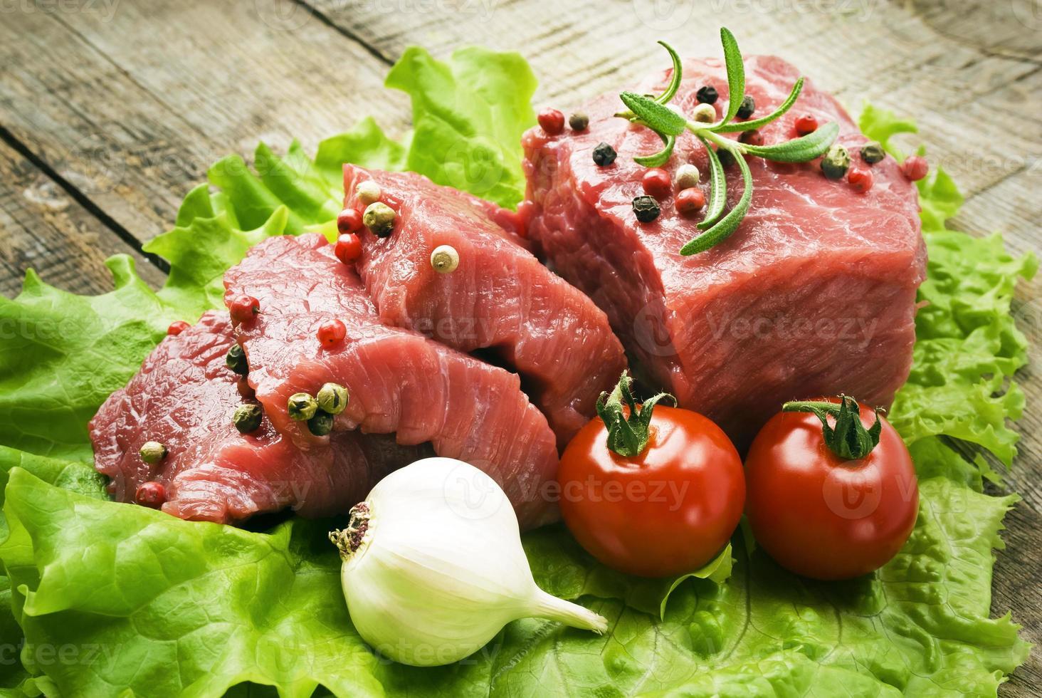 rohes Steak mit grünem Salat auf Holzbrett foto