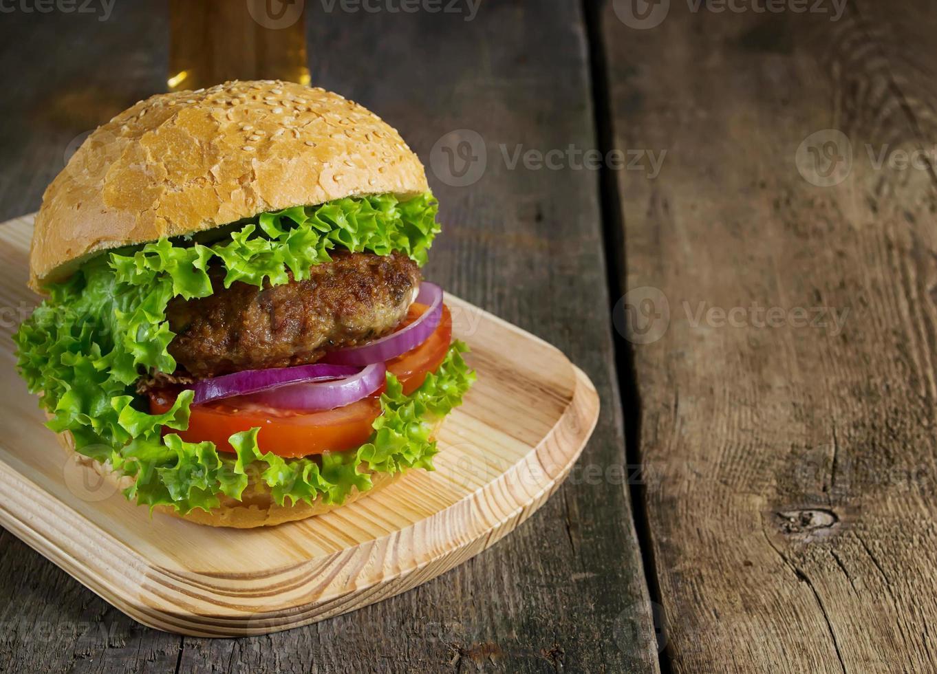 Burger mit Rinderschnitzel, Salat, Zwiebeln und Tomaten foto