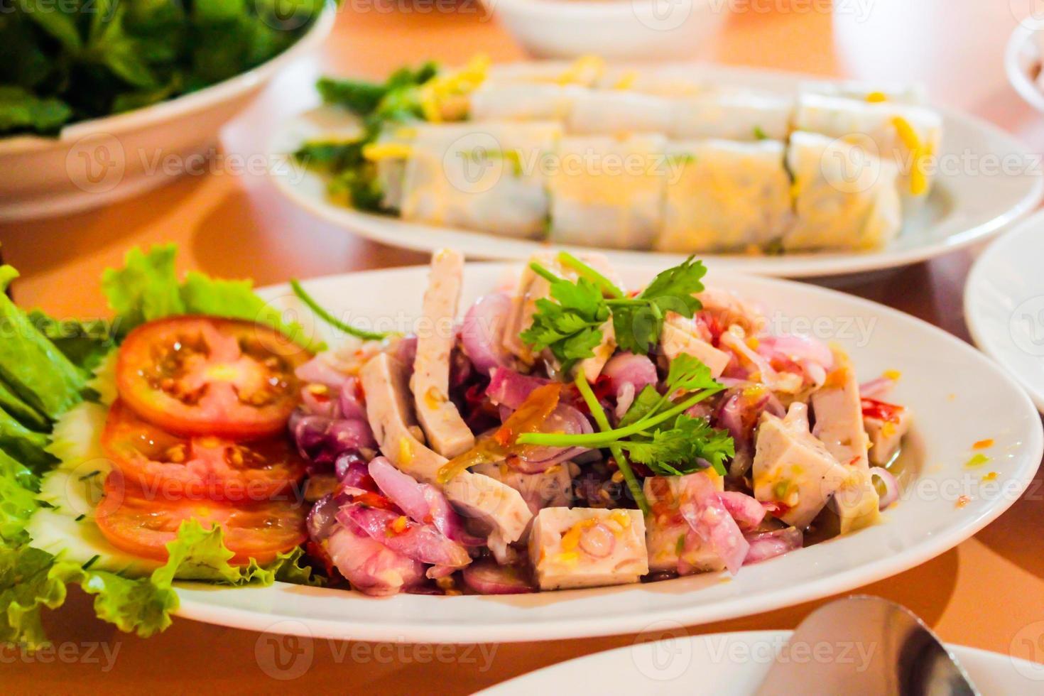 würziger Salat aus gekochter Schweinswurst, thailändisches Essen foto