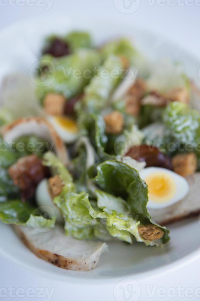 Hühnchen-Caesar-Salat mit Wachtelei, Pancetta und Parmesan-Chips. foto
