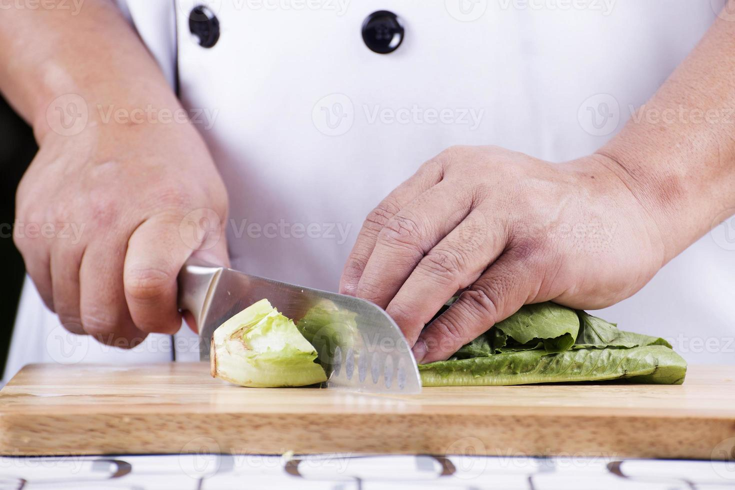 Koch schneidet grünen Salat foto