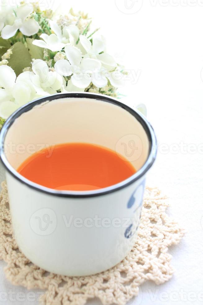 Zinnbecher und Karottensaft foto