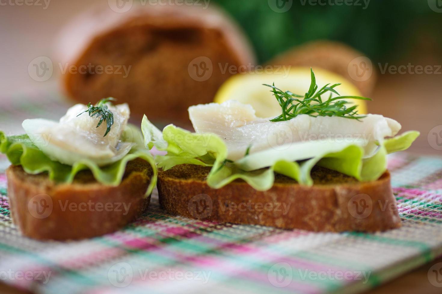 Sandwich gesalzener Hering und Salat foto