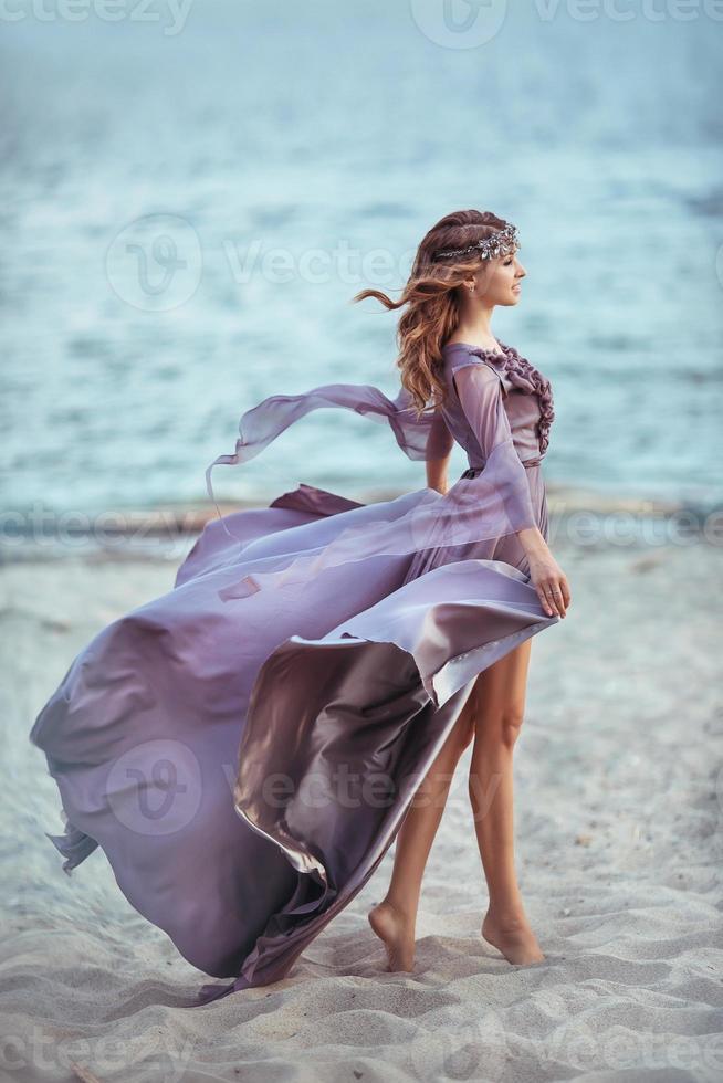 schönes Mädchen in einem feenhaften lila langen Kleid foto