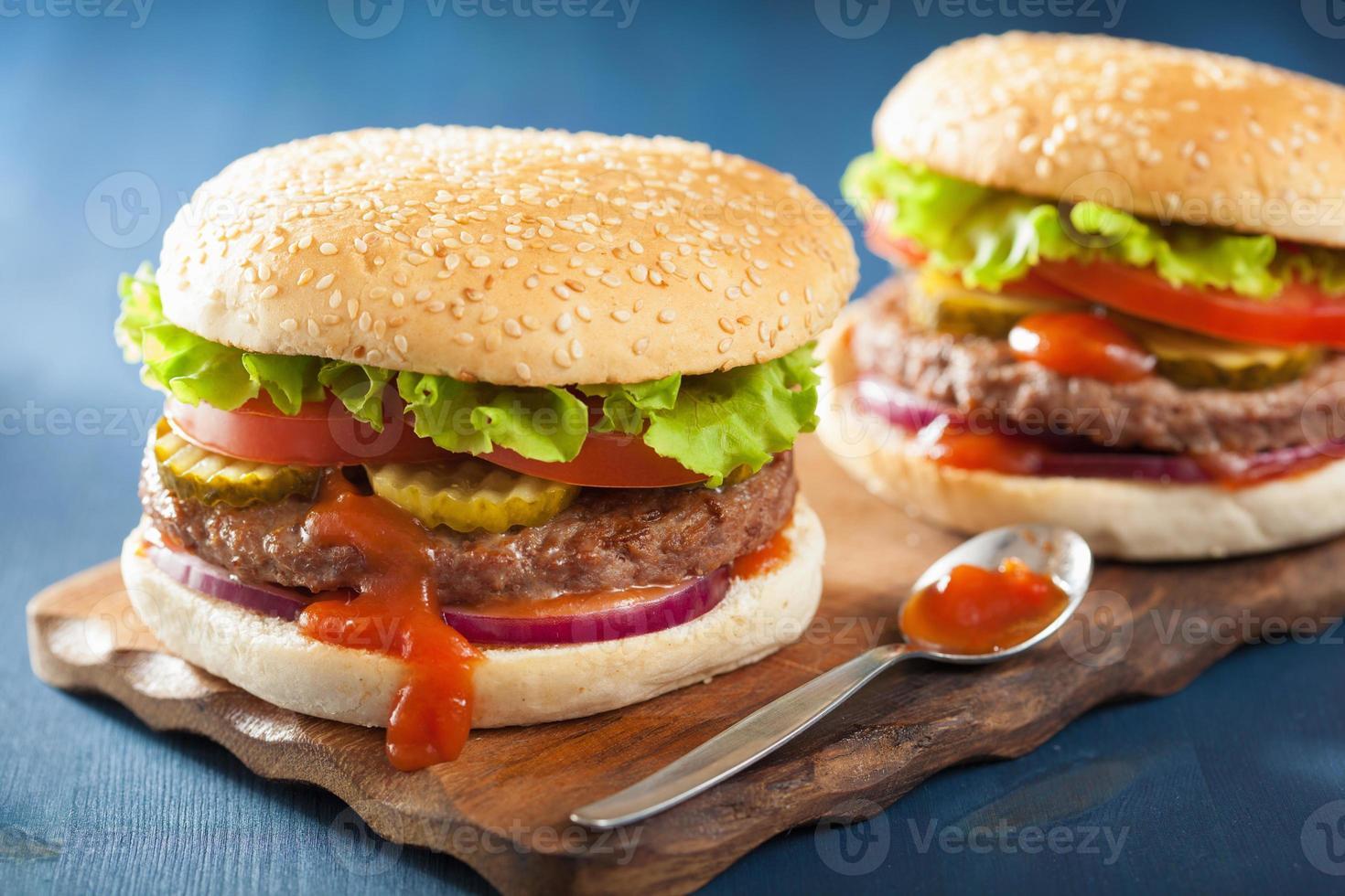 Burger mit Rinderpastetchen Salat Zwiebel Tomaten Ketchup foto