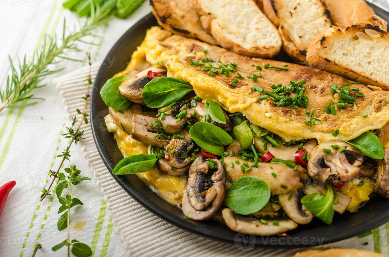 Omelett mit Pilzen, Lammsalat, Kräutern und Chili foto