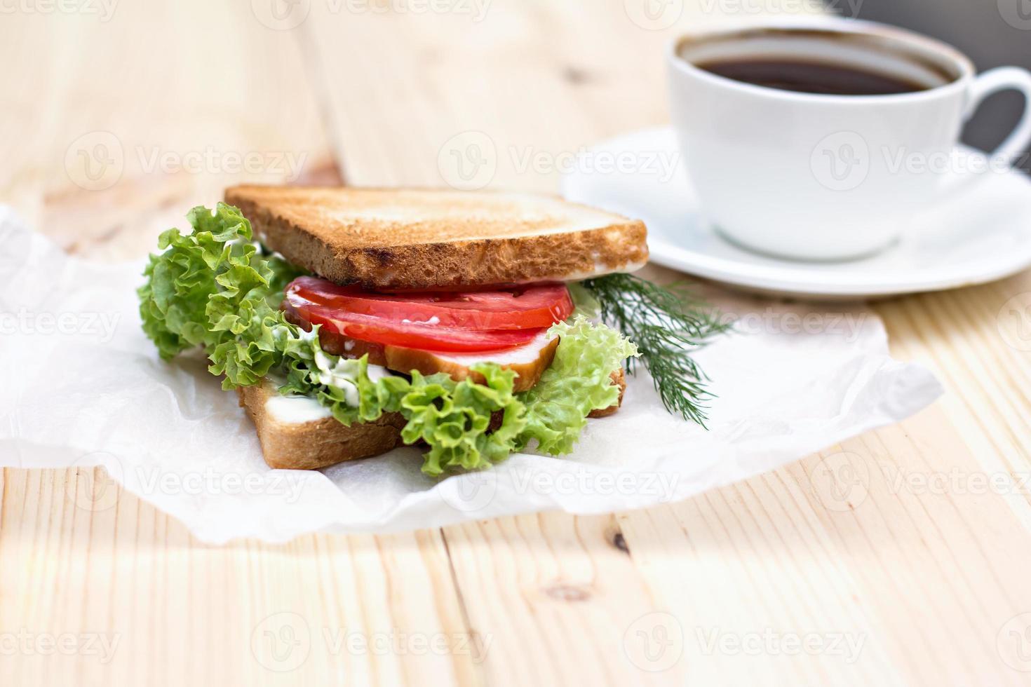 Sandwich und eine Tasse schwarzen Kaffee auf dem Tisch foto