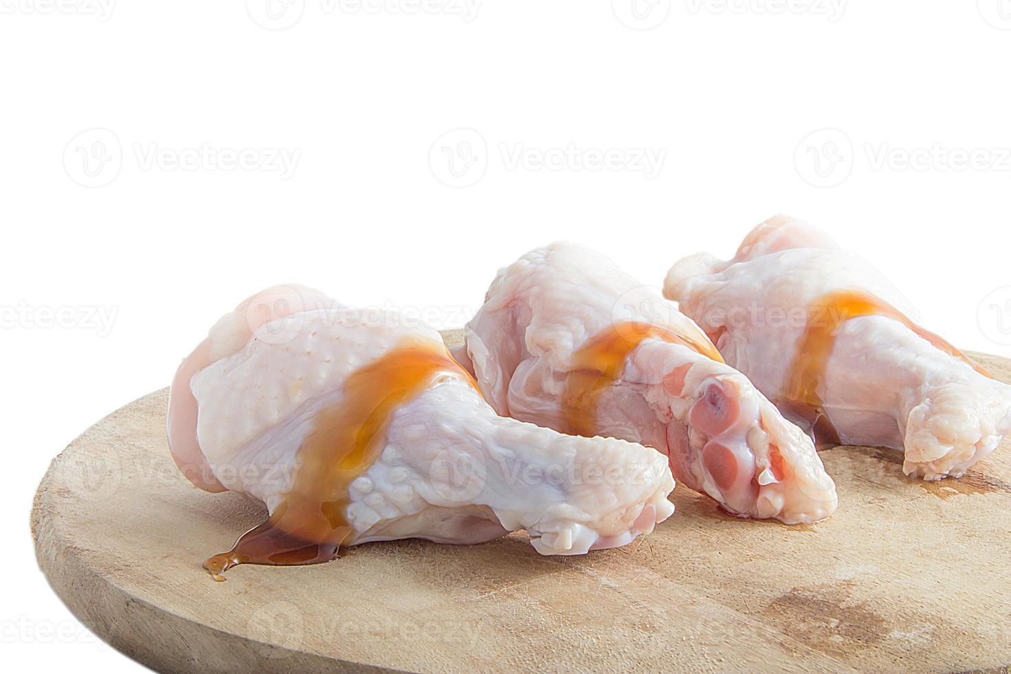 rohe Hähnchenschenkel auf hölzernen Schneidebrettern auf weißem Hintergrund foto