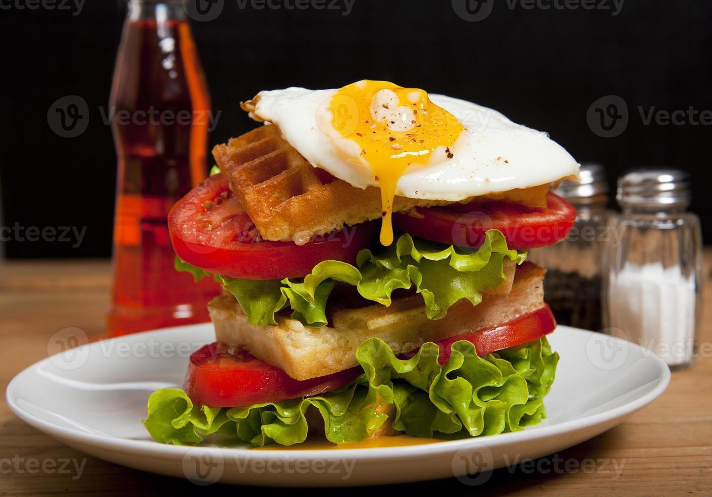 Sandwich mit Waffeln, Tomaten, Salat und Ei. mit Aperol foto