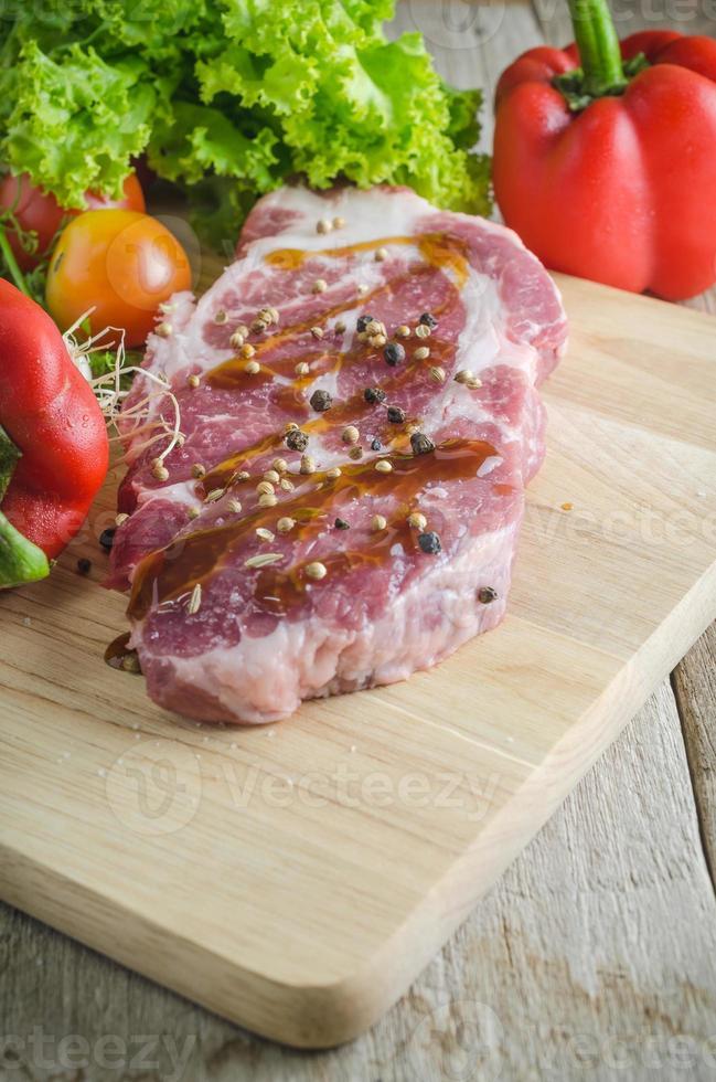 rohes Schweinefleisch auf Schneidebrett und Gemüse foto