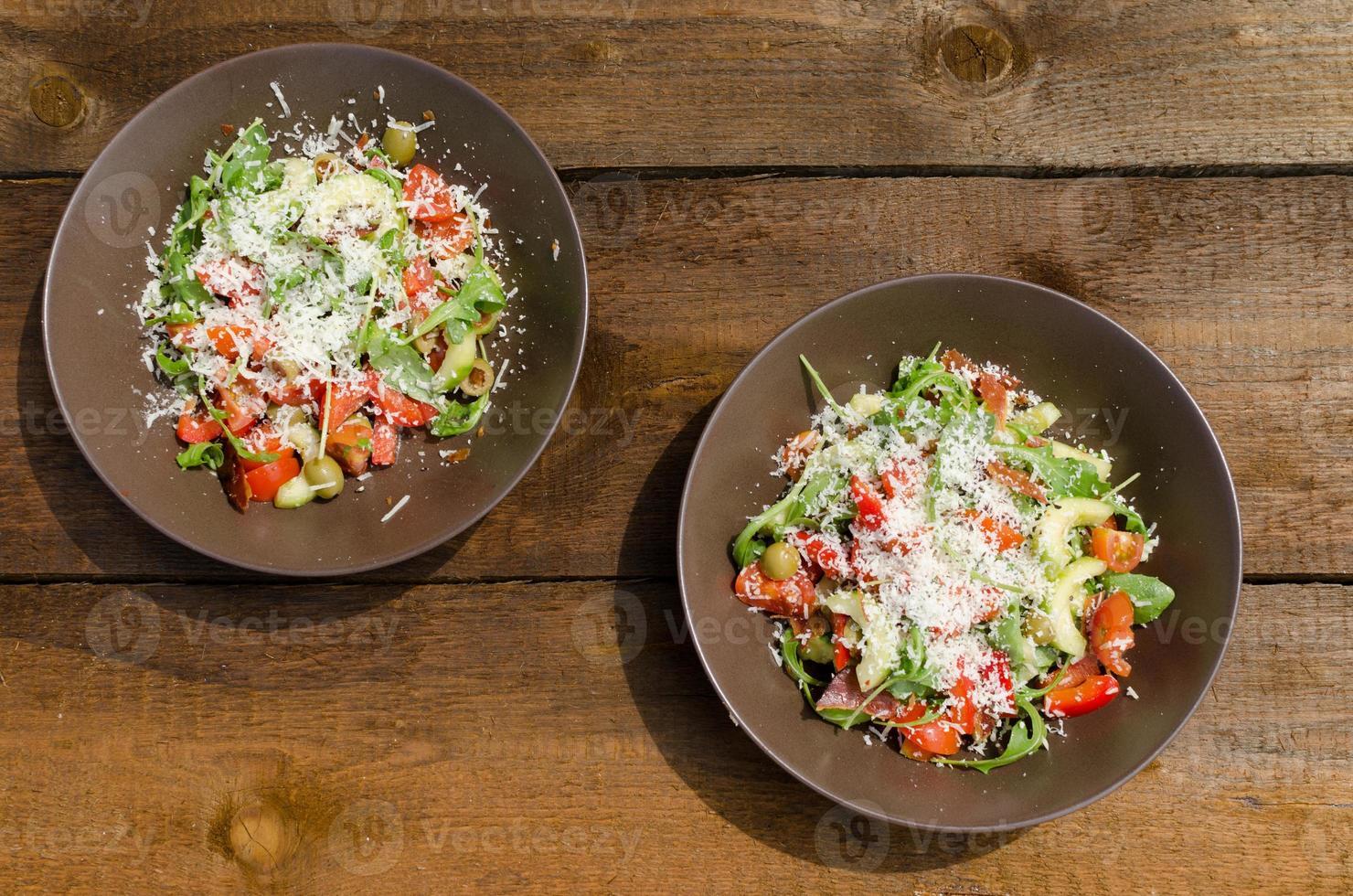 Rucola-Salat mit Tomaten, Oliven und Parmesan foto