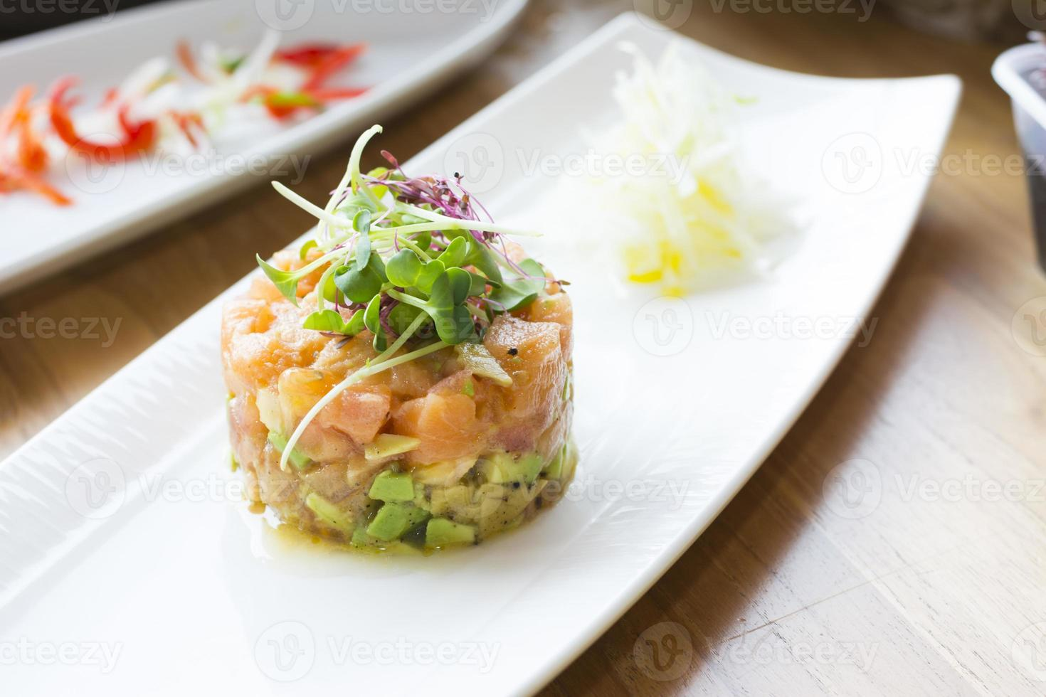 Lachstatar-Stapel mit Avocado, Oliven und Estragon foto