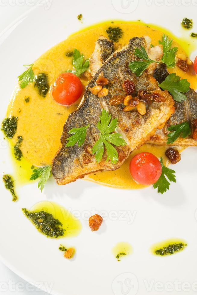Gegrillter Fisch mit Tomaten und gemischtem Salat foto