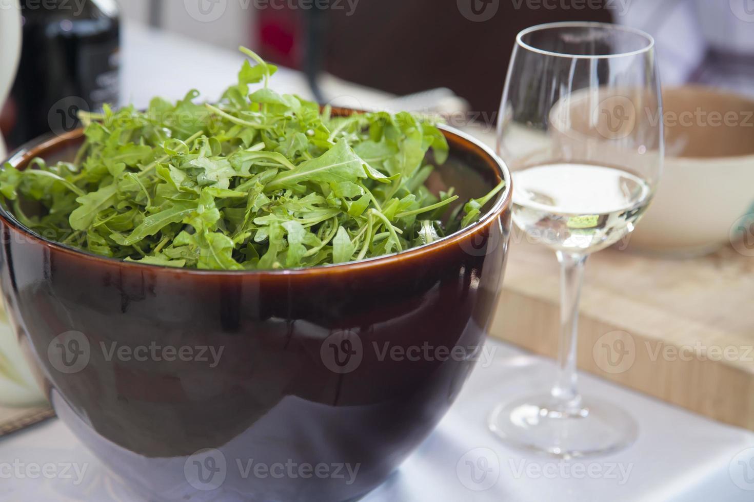 Rucola in einer Schüssel und einem Glas Wein. foto