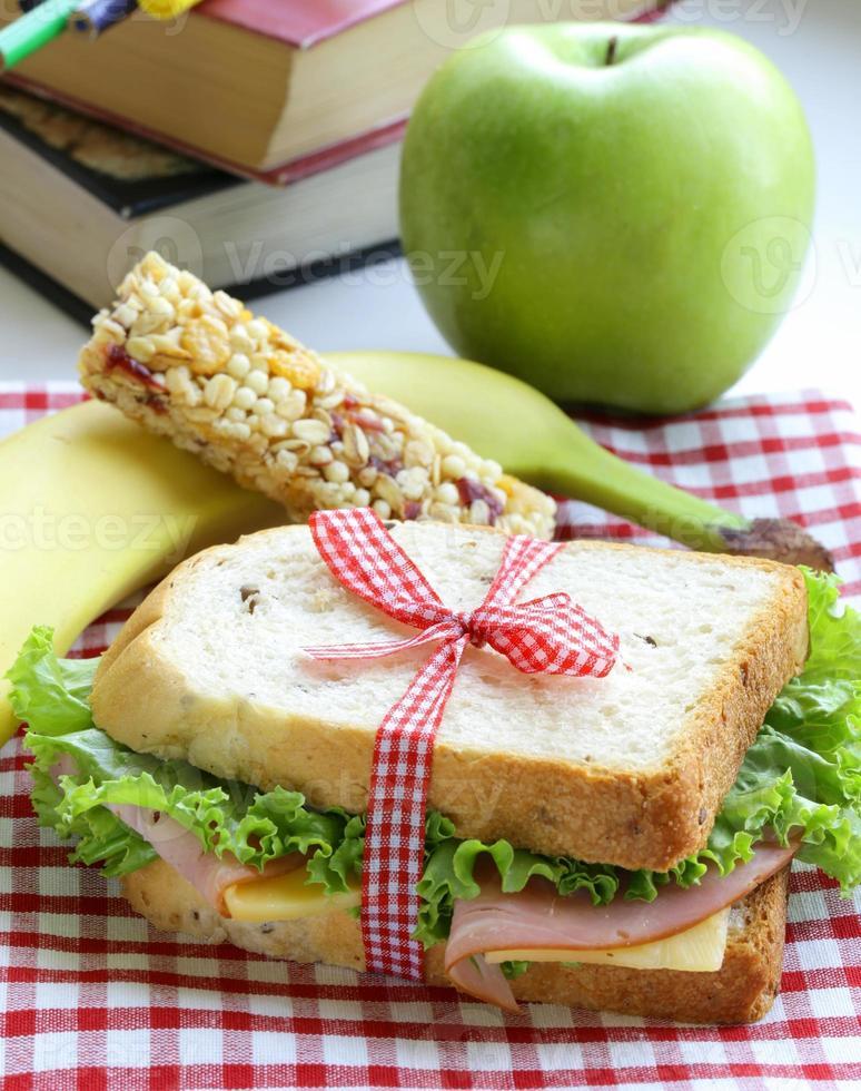 Sandwich mit Schinken, Apfel, Banane und Müsliriegel foto