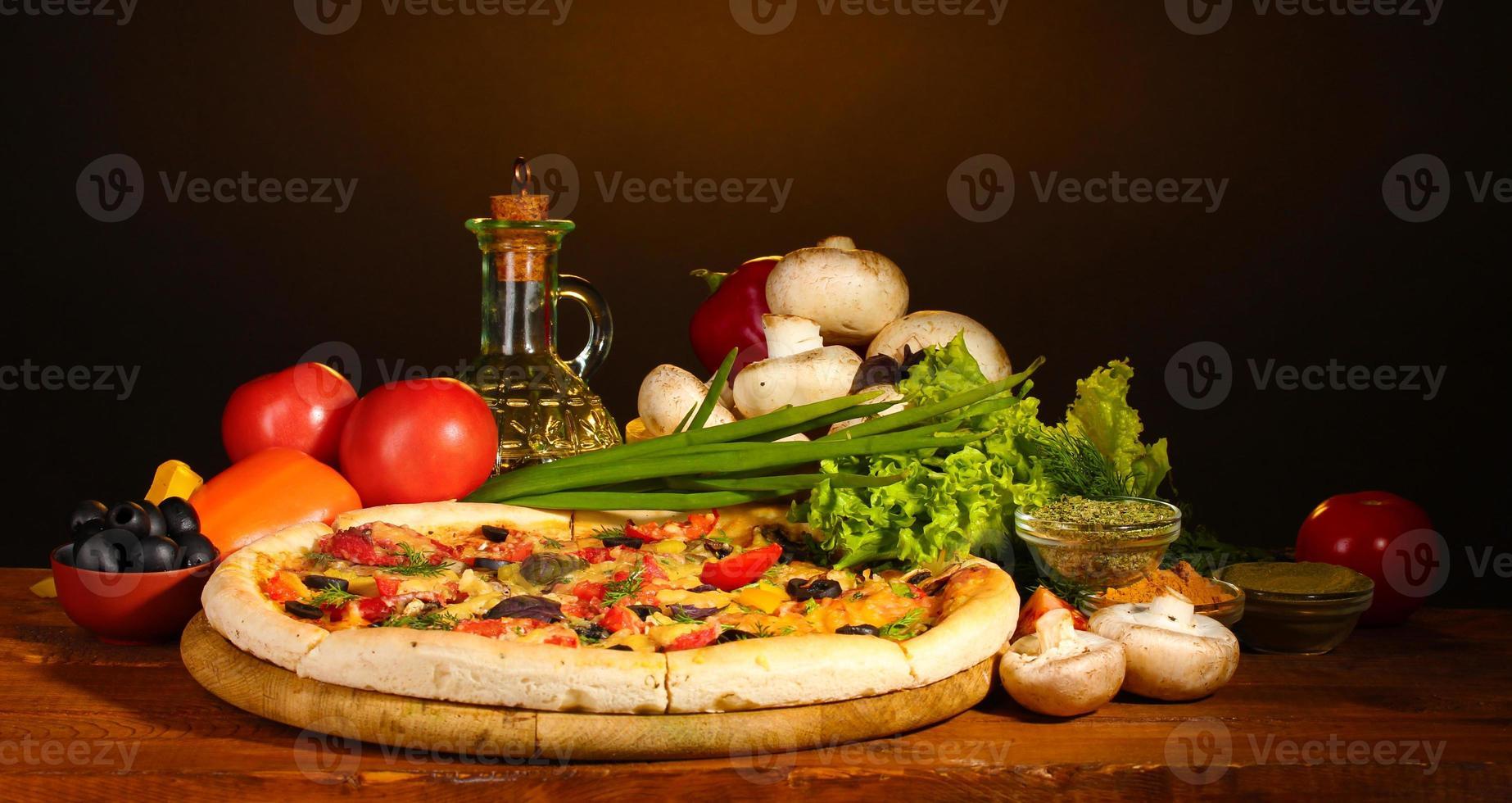leckerer Pizzateig, Gewürze und Gemüse auf Holztisch foto