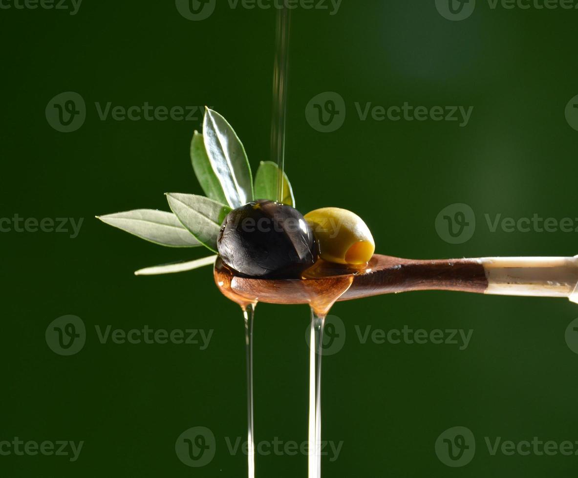 Öl fällt auf zwei Oliven mit Blättern foto