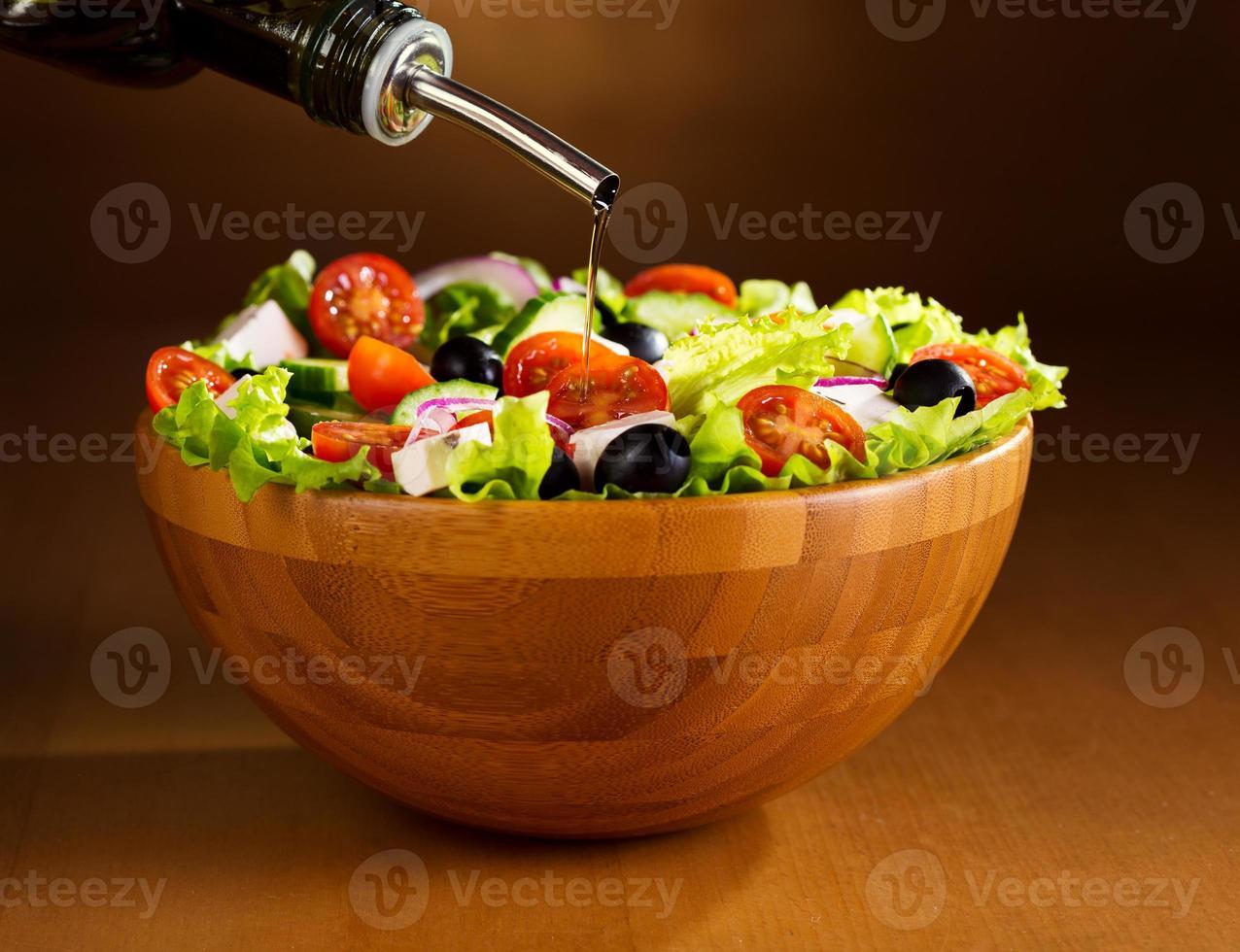 Öl in eine Schüssel Gemüsesalat gießen foto
