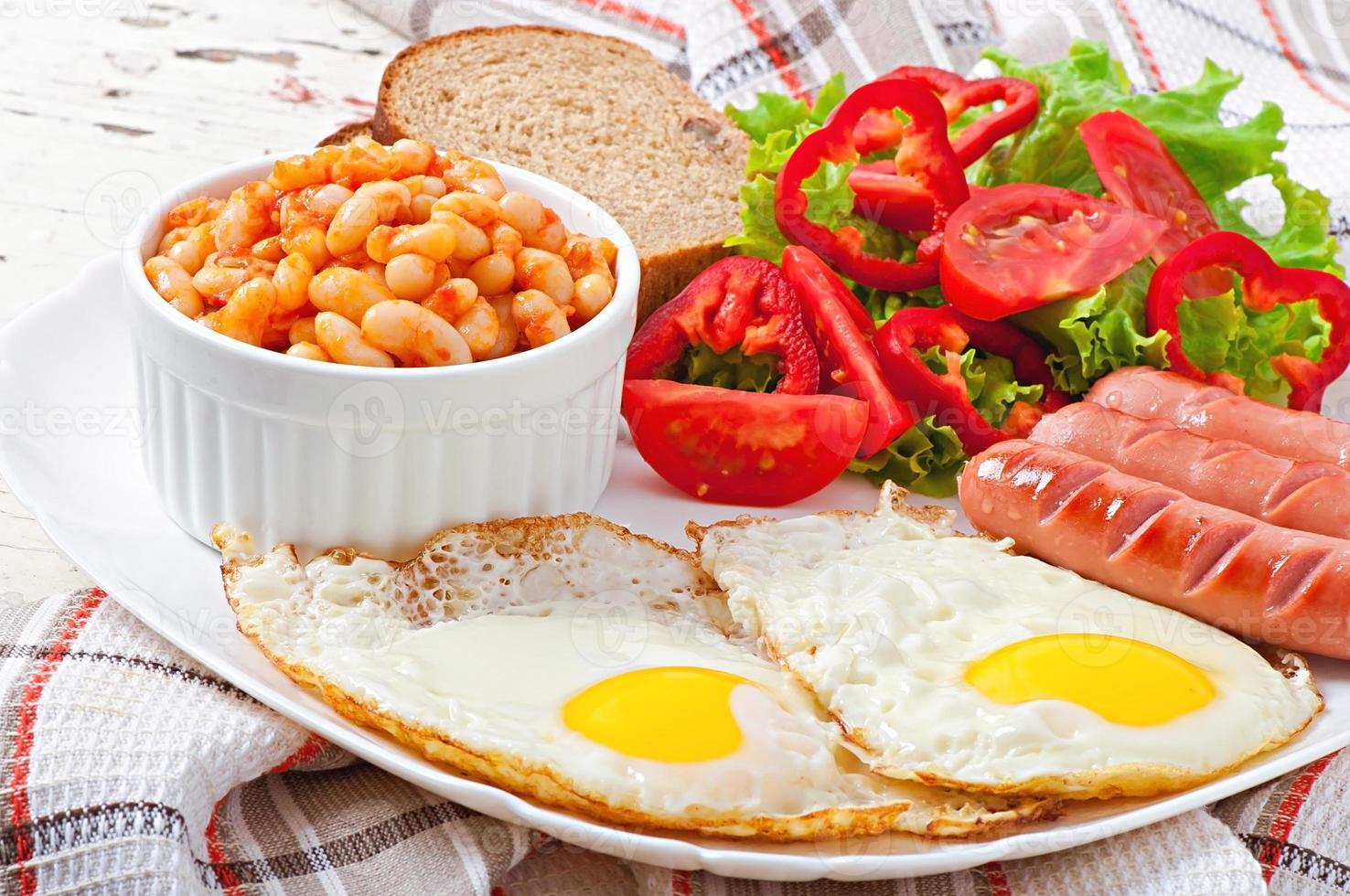 englisches Frühstück - Würstchen, Eier, Bohnen und Salat foto
