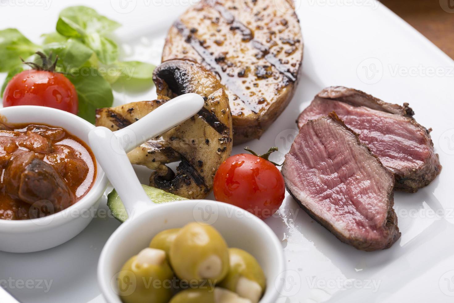 Gegrilltes Rindfleisch mit Sauce und Oliven foto