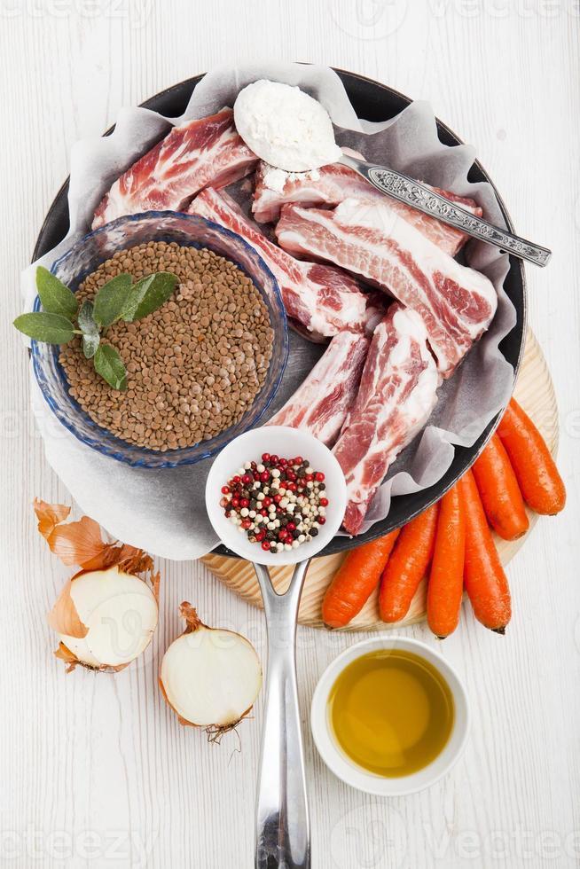 Kochzutaten in der Pfanne: rohe Rippen, grüne Linsen, Karotten, foto