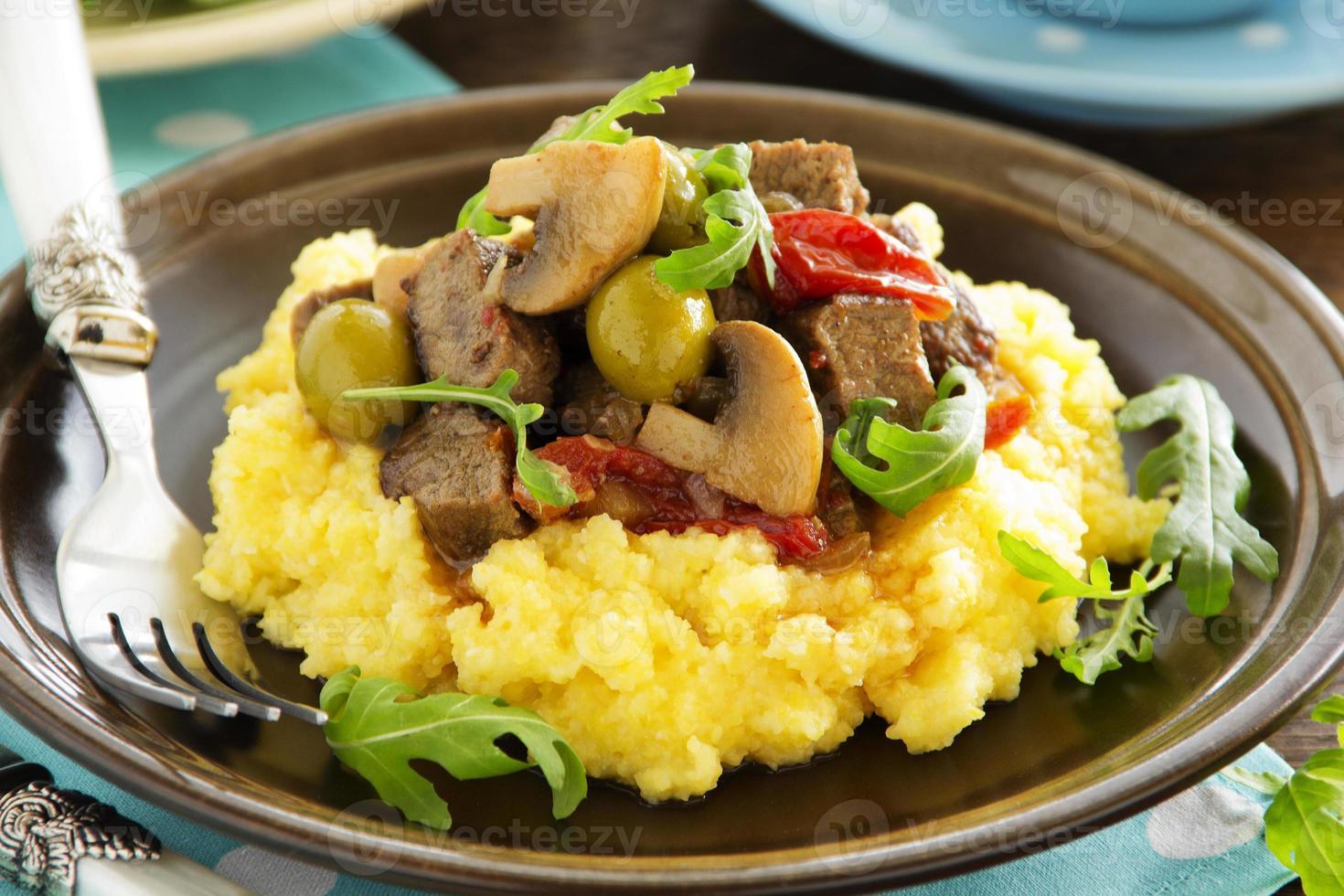köstlicher Rindfleischeintopf mit Oliven, Pilzen und Polenta. foto