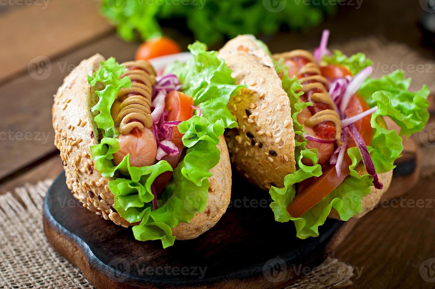Hotdog mit Ketchup-Senf und Salat auf hölzernem Hintergrund. foto