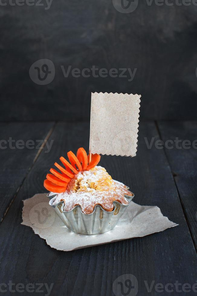 Cupcake mit leerem Etikett auf dem Holztisch foto