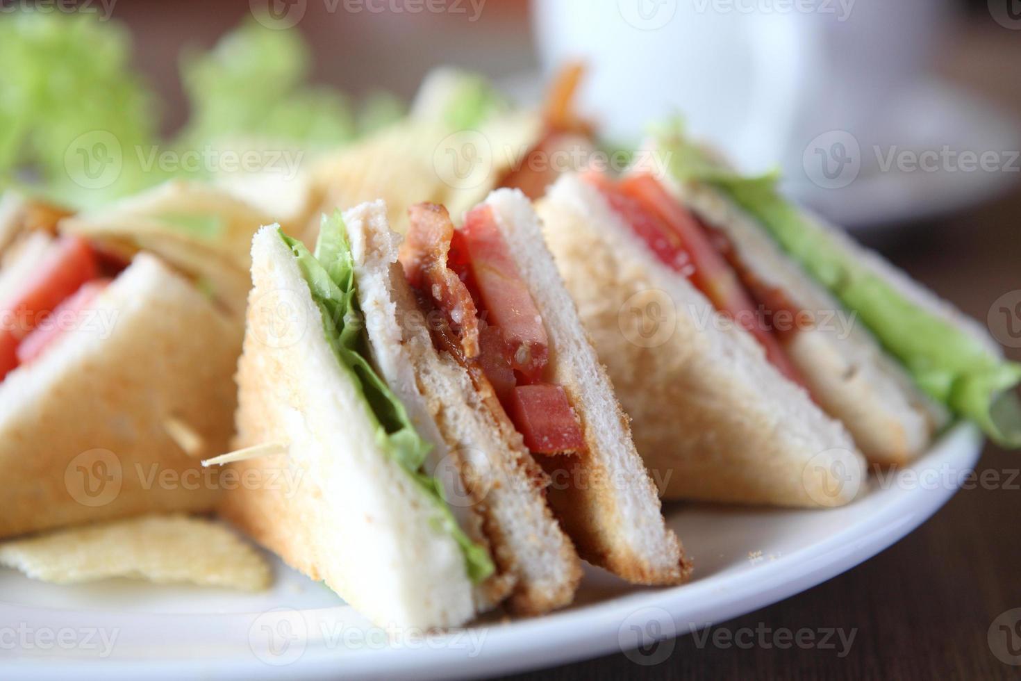 Club Sandwich mit Kaffee auf Holzhintergrund foto