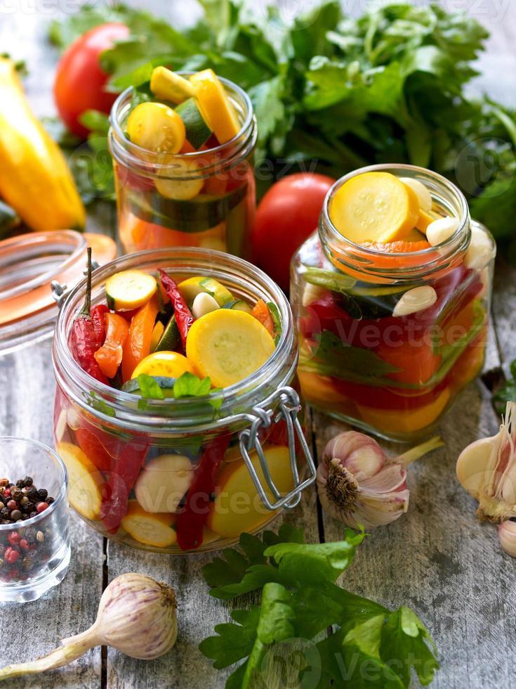 Zubereitung von eingelegten Zucchini in Gläsern mit Gewürzen und Knoblauch foto