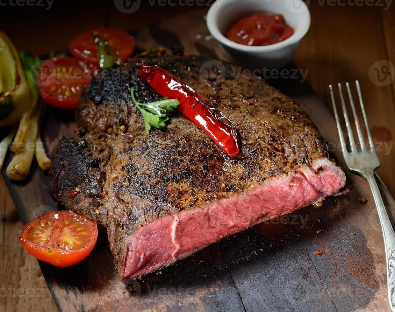 Steak auf dem hölzernen Hintergrund mit geröstetem Gemüse foto