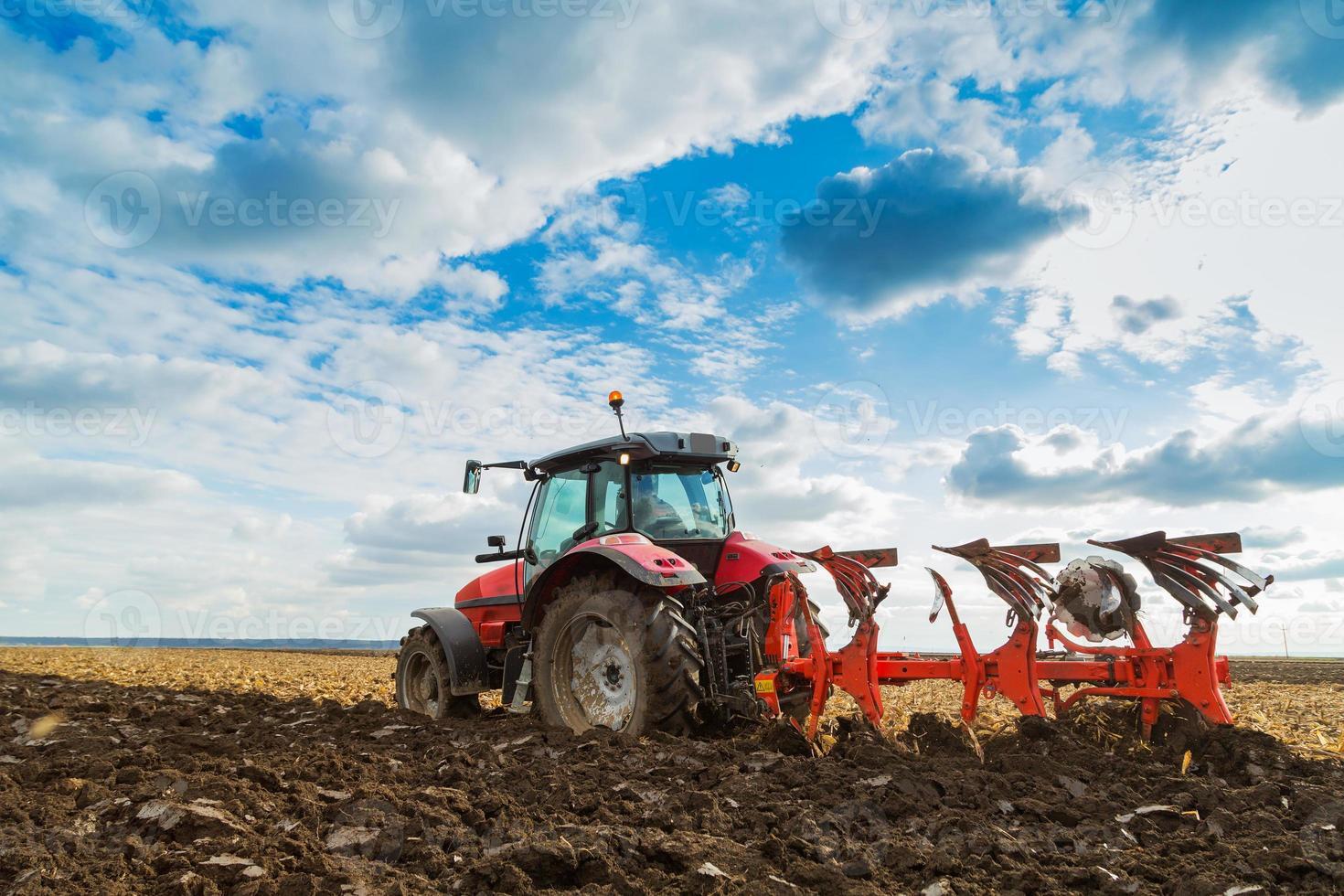 Bauernpflugfeld im roten Reittraktor foto