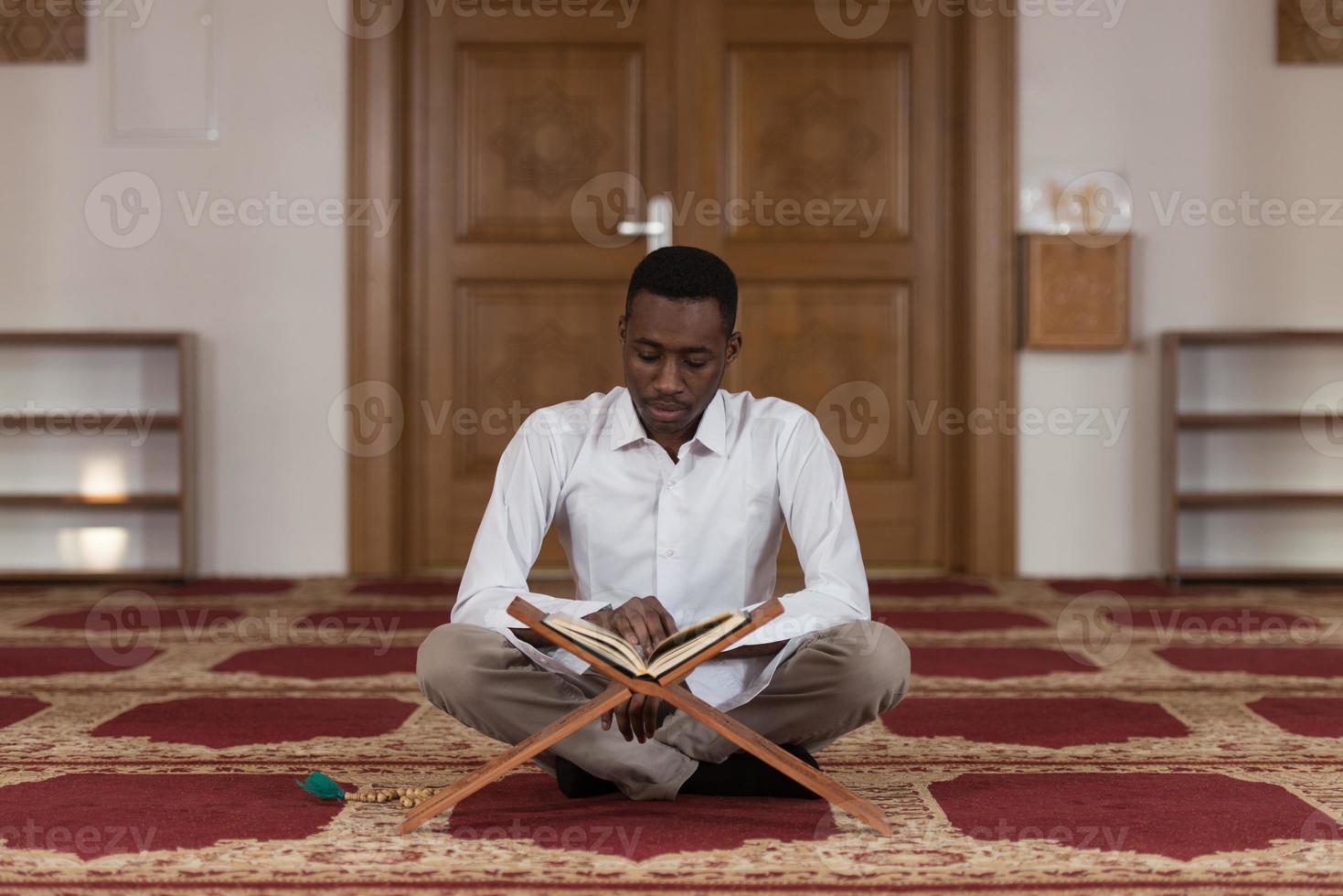 junger afrikanischer muslimischer Typ, der den Koran liest foto