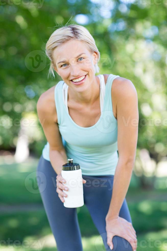 hübsche Blondine hält Flasche Wasser foto